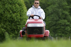 Yard Work. A man is cutting the grass on a riding tractor mower stock photo