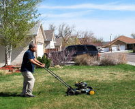 Yard work. African american male doing yard work and mowing the lawn outside Stock Photos