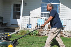 Yard work. African american male doing yard work and mowing the lawn outside Stock Images