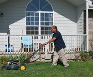 Yard work. African american male doing yard work and mowing the lawn outside Stock Photography
