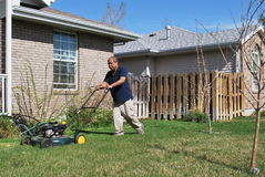Yard work. African american male doing yard work and mowing the lawn outside Royalty Free Stock Photos
