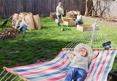 Yard work. Beautiful woman in multiple places at once cleaning and resting early spring time Royalty Free Stock Image