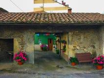 Yarda de una pequeña casa rural con flores y un banco imagenes de archivo