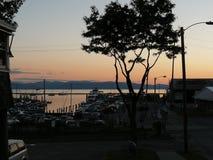 Yarda del muelle del barco contra las montañas y la puesta del sol imagenes de archivo