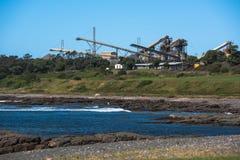 Yarda industrial del material de la refinería o de construcción por el océano Imagen de archivo libre de regalías