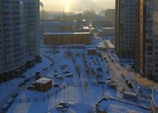 Yarda nevada de la ciudad del invierno en la puesta del sol Imagen de archivo libre de regalías