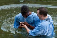 Yardenit, Israel - 29 Decembre 2012: ein Mann betet nach seiner Taufe in Jordan River Der Priester hält seine Hände lizenzfreie stockbilder