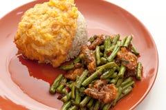 Yardlong豆搅动油煎用猪肉和辣咖喱在泰国样式,服务用米和炒蛋在板材 免版税库存图片