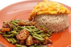 Yardlong豆搅动油煎用猪肉和辣咖喱在泰国样式,服务用米和炒蛋在板材 库存照片