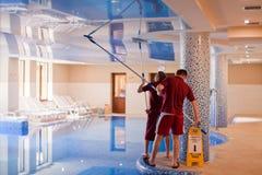 Yaremche, Ucrania - 18 de marzo de 2015: Dos hombres limpian el techo de la piscina Imagen de archivo