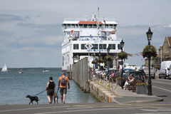 YARMOUTH HARBOUR ISLE OF WIGHT ENGLAND UK. A roll on roll off ferry berthed on the waterfront and passengers walk their pet dogs before embarking stock image