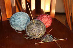 Yarn balls and knitting. 3 balls of yarn in the early morning sun with the beginning of a knitting project Stock Photography