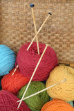 Yarn Basket. A basket of brightly colored yarn and wooden knitting needles royalty free stock images