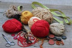 Yarn bolas, botões e um centímetro em uma tabela de madeira foto de stock