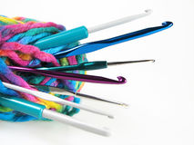 Yarn with crochet hooks. Close up to ball of yarn with different sizes of crochet hooks placed over white stock image
