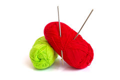 Yarn and hooks for knitting. The photo shows two skeins of yarn. In a skein of yarn of red color hooks for knitting are stuck Royalty Free Stock Images