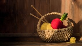 Yarn with hyacinth in basket with kniting sticks on old wooden background. Vintage royalty free stock photos
