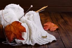 Yarn and knitting needles. Balls of white yarn in a basket with knitting needles, autumn concept Royalty Free Stock Images