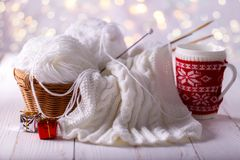 Yarn and knitting needles. Balls of white yarn in a basket with knitting needles and cup of coffee on wooden background Stock Photography