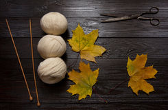 Yarn, knitting needles, scissors and yellow leaves on a table. Three skeins of white yarn, wooden knitting needles, scissors and yellow leaves are a dark brown Stock Photography