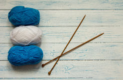 Yarn and knitting needles are on a white wooden table. Knitting. Skeins of yarn and knitting needles are on a white wooden table. Top view Royalty Free Stock Images
