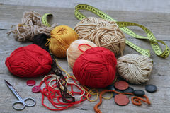 Yarn le palle, i bottoni e un centimetro su una tavola di legno Fotografia Stock