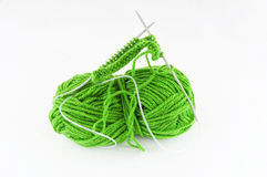 Yarn and needles for kniting. Green and yarn and needles and piece of knitting Royalty Free Stock Photography
