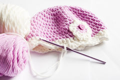 Yarn and pink baby hat Royalty Free Stock Image
