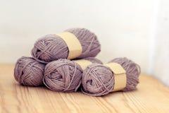 Yarn rolls. Grey yarn on wood background Stock Photo
