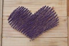 Yarn shape of heart on wooden board Stock Photo