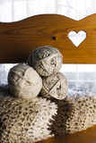 Yarn Skeins and Afghan on wood Bench. Three neutral colored yarn skeins and a crocheted afghan on a wood bench with a heart cutout Stock Photos