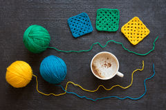Yarn of three colors, crocheted motives and coffee Stock Photo