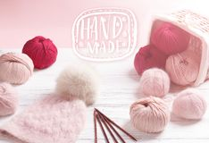 Yarn in wicker basket on white wooden background. Lettering hand made Royalty Free Stock Photo