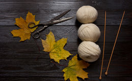 Yarn, wooden knitting needles, scissors and yellow leaves. Three skeins of white yarn, wooden knitting needles, scissors and yellow leaves are a dark board. Top Royalty Free Stock Images