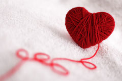 Yarn of wool in heart shape symbol. Red heart shape symbol made from wool on textured white background stock image