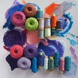 Yarns of threads for knitting in different colors on a palette. Background Stock Images