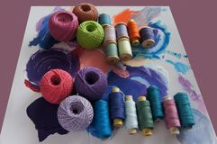 Yarns of threads for knitting in different colors on a palette. Background Stock Photos