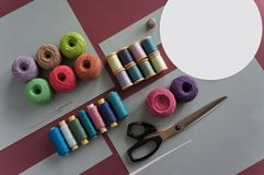 Yarns of threads for knitting in different colors on a pink and grey. Background Stock Photography