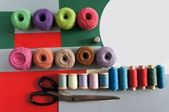 Yarns of threads for knitting in different colors on a red green. Background Royalty Free Stock Images