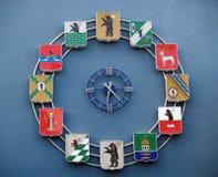 YAROSLAVL, РОССИЯ Часы с гербами городов региона Yaroslavl на строя стене стоковые изображения