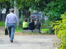 Yaroslavl, Rusia - hombre que pasa por tres personas que se sientan en un bloque de cemento fotografía de archivo libre de regalías