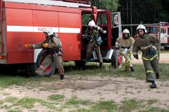 Firefighters jump out and run from the cab of the fire truck stock photography