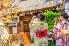 Yasaka Shrine Geisha. Japanese women in kimono take picture of Yasaka Shrine also known as Gion Shrine, one of the most famous shrines in Kyoto, Japan, between Stock Image