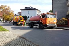 Yaslo,波兰- 9 9 2018年:污水清洁通过在一个小欧洲镇的街道上的特别技术手段 橙色汽车和自治都市 免版税库存图片
