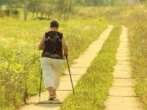 Yaslo, Polônia - 9 de julho de 2018: Escandinavo/passeio nórdico Uma mulher na roupa da cidade dá uma volta através da grama do ` imagens de stock royalty free