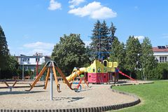 Yaslo, Poland - july 12 2018: Children`s playground in the park amidst greenery. Multicolored swings and buildings for children fr stock photo