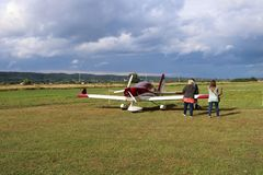 Yaslo, Poland - july 3 2018:The family at the airport is near a light two-seater turboprop aircraft of red color. Airshow free tim royalty free stock photography