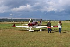 Yaslo, Poland - july 3 2018:The family at the airport is near a light two-seater turboprop aircraft of red color. Airshow free tim stock photo