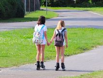 Yaslo, Poland - july 10 2018: Two girls rollerblading holding hands. Active lifestyle. Children on summer vacation. Fashionable ch stock photos