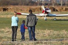 Yaslo, Polen - 9 3 2019: Die Familie am Flughafen ist nahe einem hellen Zweisitzerturboprop-triebwerk Flugzeug der roten Farbe Ai lizenzfreies stockbild